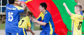 4 boys taking part in a PE lesson playing with a multi-coloured parachute
